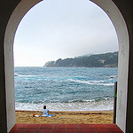 woman contemplating the sea framed by an arch""